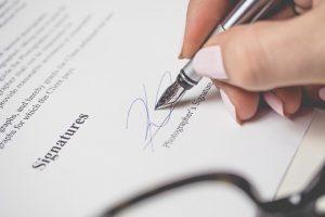契約書にサインする女性の手の画像