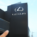 LEXUS,レクサスショールームの外看板を指さす画像