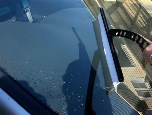 車のフロントガラスをプロスタッフポリマーメンテナンスシリコンワイパーで水切りする画像