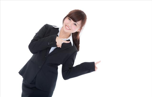 笑顔で指をさすスーツの女性の画像